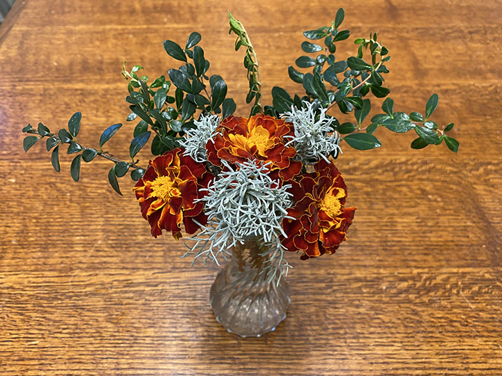 Bouquet with a pleasing color combination of silver, dark green, and orange.